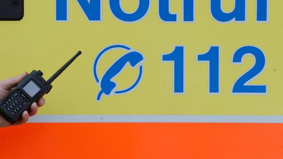 Ein Sanitäter vor einem Rettungswagen mit der Nummer des Notrufes. Foto: Jens Kalaene/dpa-Zentralbild/dpa/Symbolbild