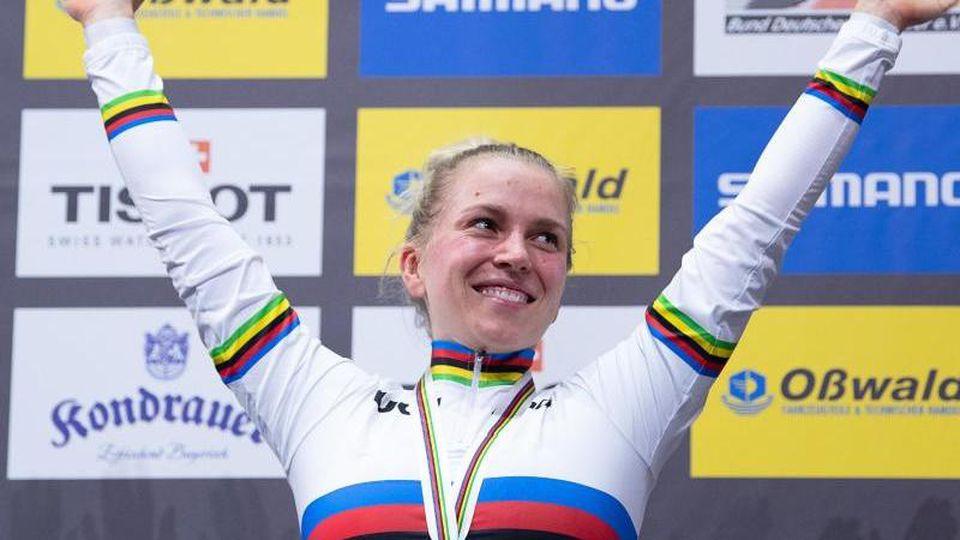 Emma Hinze freut sich auf dem Podium über den Sieg. Foto: Sebastian Gollnow/dpa/Archivbild