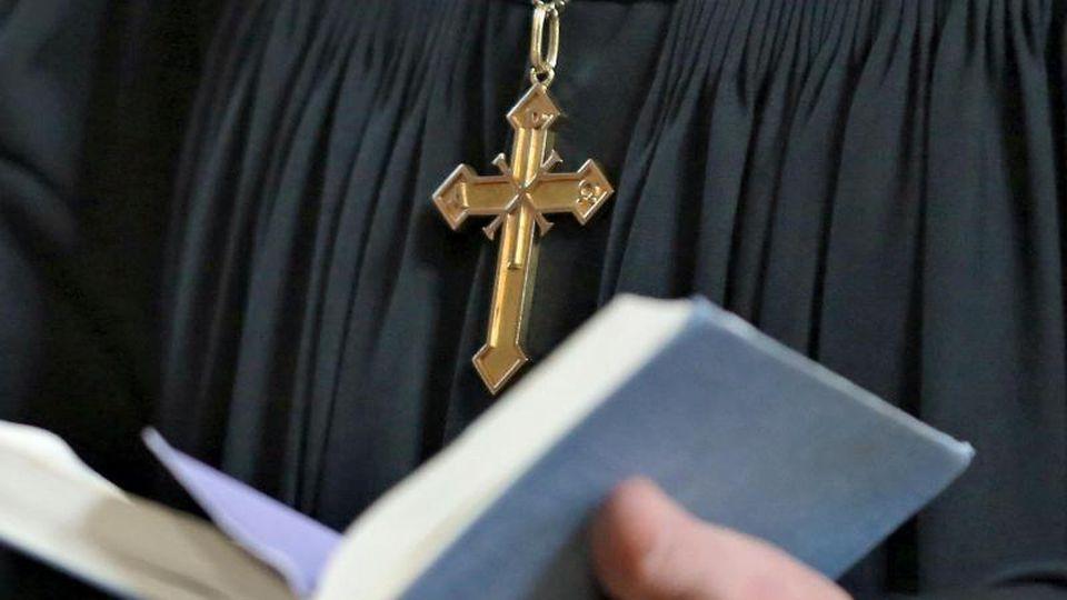 Ein Geistlicher hält beim Gottesdienst eine Bibel. Foto: Jan Woitas/zb/dpa/Symbolbild