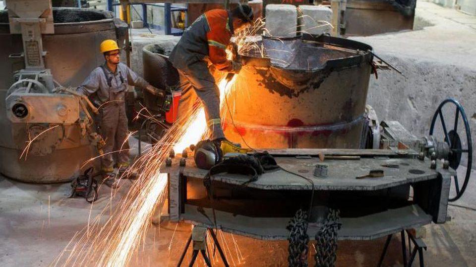 Funken sprühen bei Arbeiten in einer Gießerei. Foto: Jens Büttner/zb/dpa/Archivbild
