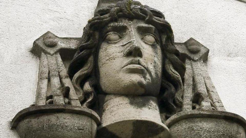 Eine Justitia-Büste ist an der Fassade eines Gerichts zu sehen. Foto: Ina Fassbender/Archiv