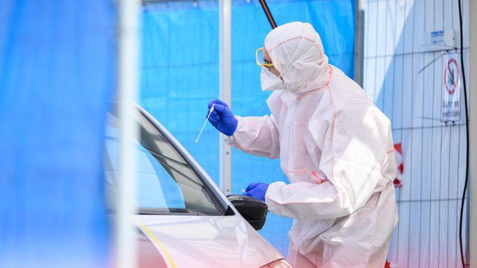Ein Mitarbeiter führt in einem Abstrichzentrum einen Corona-Test durch. Foto: Sebastian Gollnow/dpa/Symbolbild