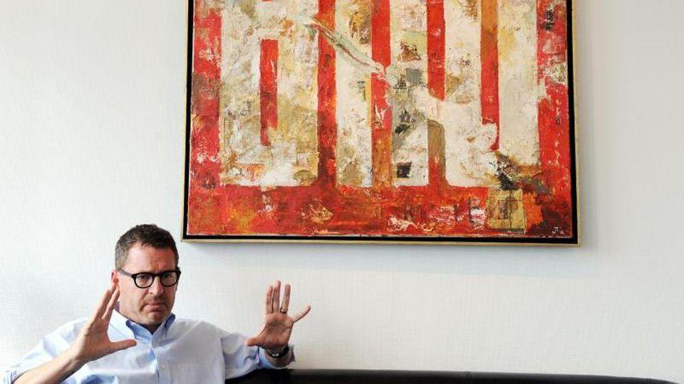 """Kai Diekmann, damaliger Chefredakteur der """"Bild""""-Zeitung, sitzt unter dem Bild von Künstler Jens Lorenzen. Foto: Maurizio Gambarini/Archiv"""