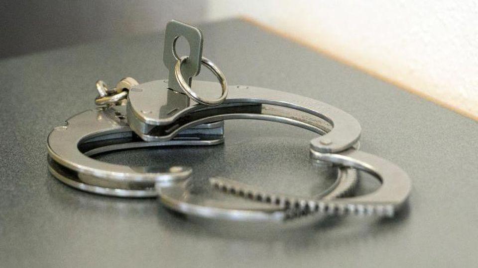 Handschellen liegen auf einem Tisch. Foto: Armin Weigel/dpa/Symbolbild