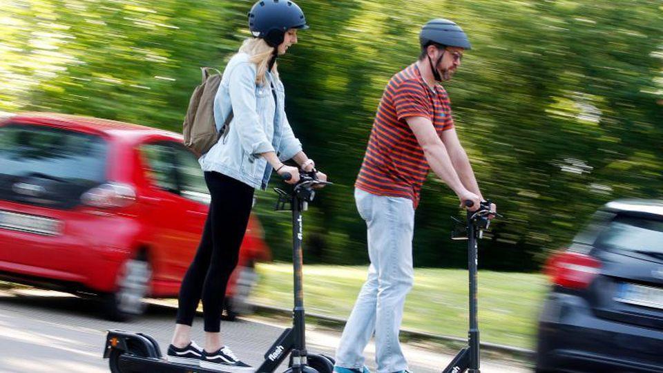 Zwei Personen fahren mit E-Scootern. Foto: Roland Weihrauch/dpa