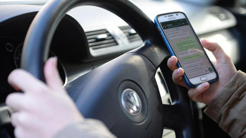 Ein Mensch sitzt am Steuer eines Autos und bedient ein Smartphone. Foto: Monika Skolimowska/dpa/Archivbild