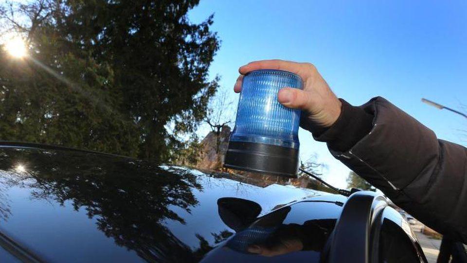 Ein Polizist setzt ein mobiles Blaulicht auf das Dach eines Autos. Foto: Karl-Josef Hildenbrand/Archivbild