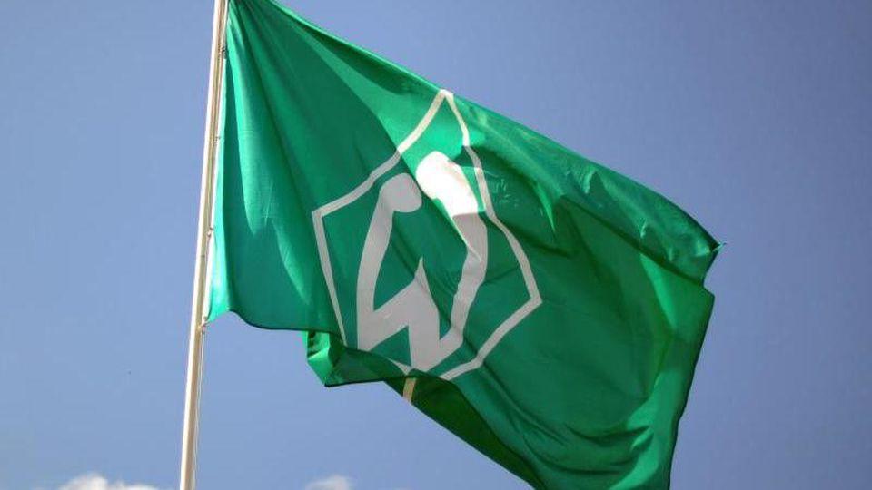 Eine Fahne mit dem Vereinslogo des SVWerder Bremen weht vor blauem Himmel. Foto: picture alliance / dpa/Archivbild