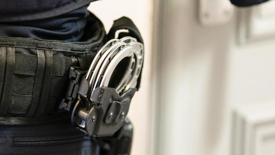 Handschellen sind an einem Gürtel eines Polizisten befestigt. Foto: Frank Molter/dpa