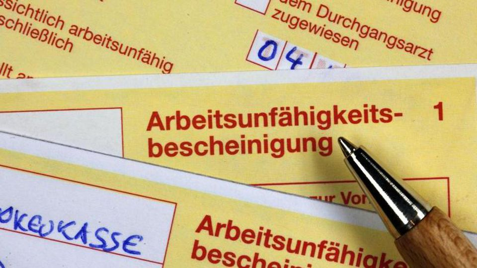 Krankenscheine liegen einem Schreibtisch. Foto: Jens Büttner/dpa-Zentralbild/dpa/Illustration