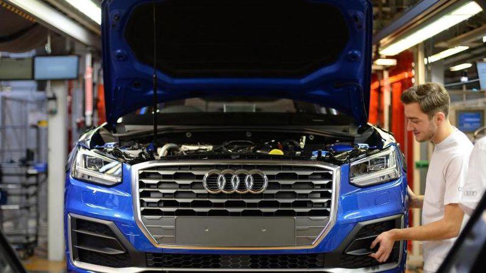 Ein Mitarbeiter bringt an einem Fließband im Audi-Werk das Frontende an einem Audi an. Foto: Andreas Gebert/dpa/Archivbild
