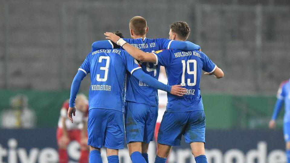 Kieler Helden feiern den Einzug ins DFB-Pokal-Halbfinale auf dem Platz - und später auch im Bus. Foto: Martin Meissner/AP POOL/dpa