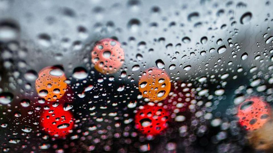 Regentropfen sind auf der Frontscheibe eines Fahrzeugs zu sehen. Foto: Peter Steffen/dpa/Archivbild