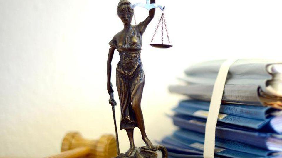 Die modellhafte Nachbildung der Justitia steht neben einem Holzhammer und einem Aktenstapel. Foto: Volker Hartmann/dpa/Symbolbild