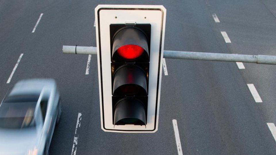 Ein Auto fährt an einer roten Ampel vorbei. Foto: Julian Stratenschulte/dpa