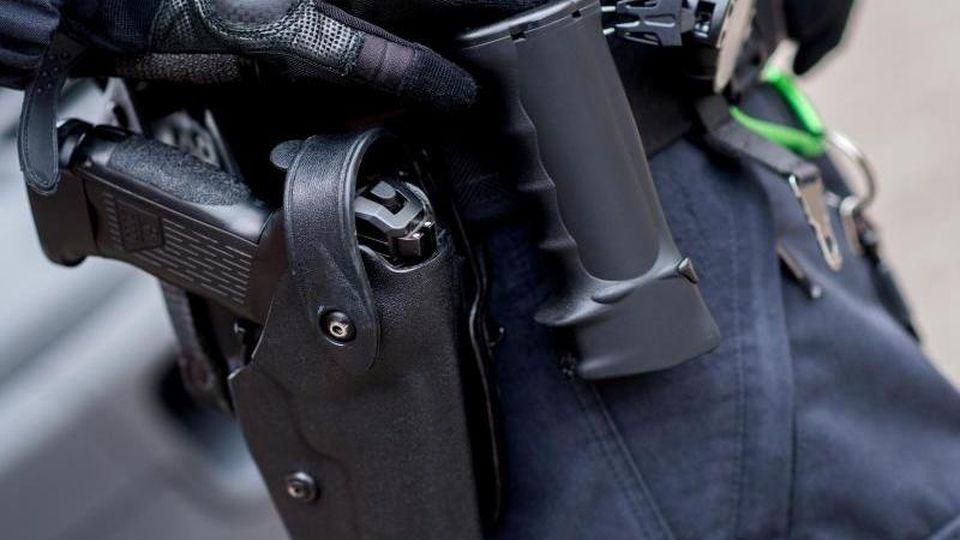 Ein Beamter trägt die Dienstwaffe am Gürtel. Foto:Hauke-Christian Dittrich/Archivbild