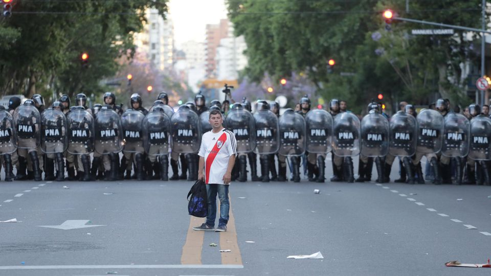 FILE PHOTO: Soccer Football - Copa Libertadores Final - Second leg - River Plate v Boca Juniors - November 24, 2018 - A fan of River Plate walks in front of riot police after the match was postponed.  REUTERS/Alberto Raggio/File Photo