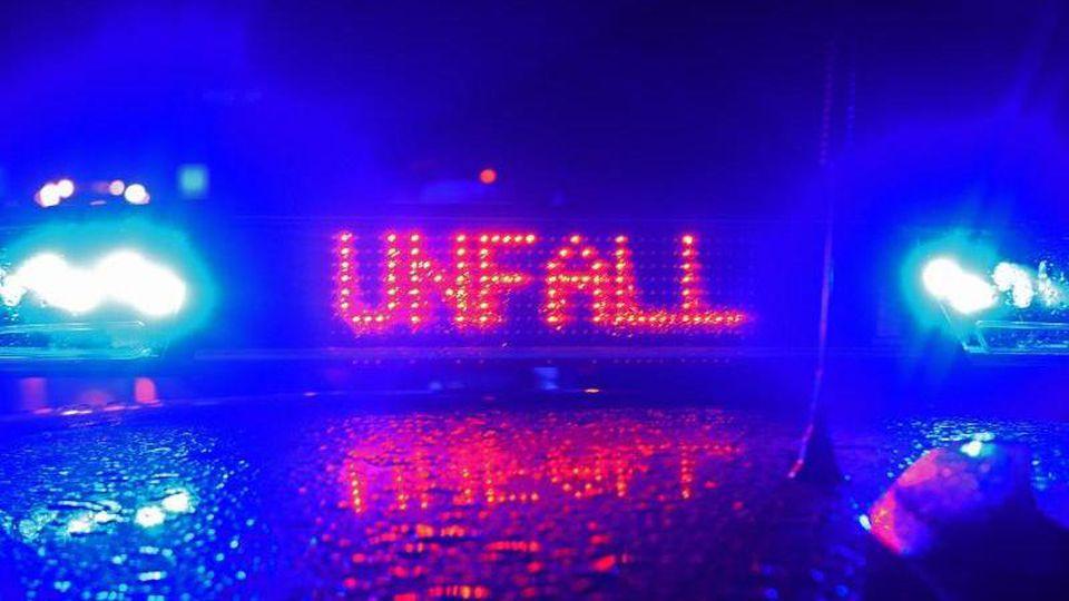 """Während einer Unfallaufnahme spiegeln sich das Blaulicht und der Schriftzug """"Unfall"""" auf dem Dach eines Polizeiwagens. Foto: Stefan Puchner/dpa"""