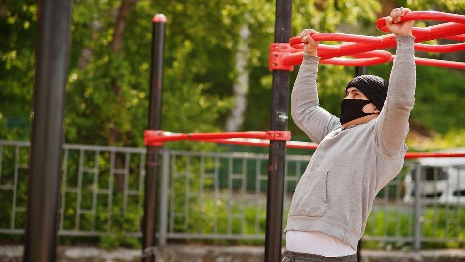 Sportler trainiert in Outdoor-Fitness-Bereich