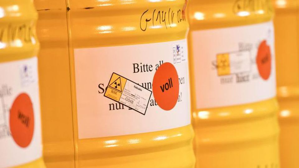 """Atommüll-Fässer mit der Aufschrift """"voll"""" stehen in einem Zwischenlager. Foto: Uwe Anspach/picture alliance/dpa/Archiv/Symbolbild"""