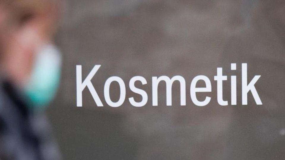 """""""Kosmetik"""" steht auf einer Eingangstür eines Kosmetikstudios. Foto: Stefan Sauer/dpa/Symbolbild"""