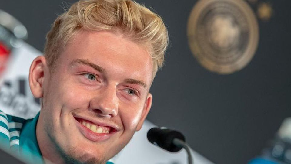 Stürmer Julian Brandt lacht während einer Pressekonferenz. Foto: Peter Kneffel/Archiv
