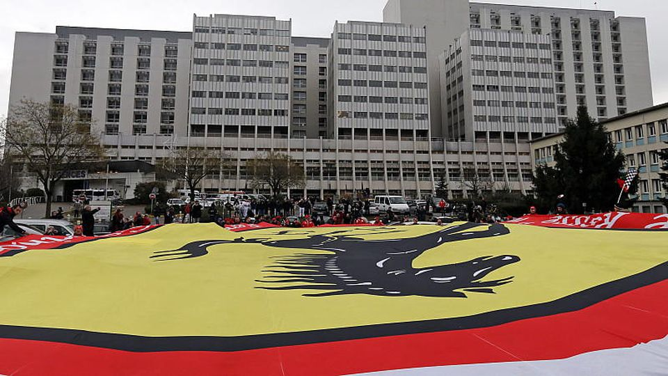 epa04006912 On the day of Michael Schumacher's 45th birthday, Ferrari fans wave a giant flag in a vigil for retired Formula One German racing driver Michael Schumacher outside the 'Centre Hospitalier Universitaire' (CHU) hospital in Grenoble, France,
