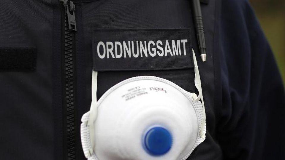 Ein Mitarbeiter des Ordnungsamtes trägt eine Atemschutzmaske an seiner Weste. Foto: Ronny Hartmann/dpa/Archivbild