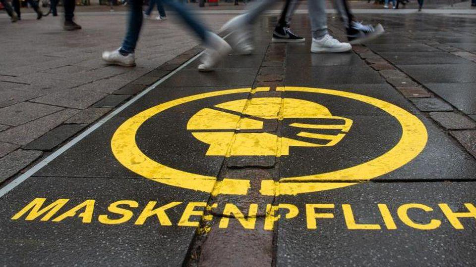 Ein Piktogramm weist in Hamburg auf die Maskenpflicht hin. Foto: Daniel Bockwoldt/dpa/Symbolbild/Archiv