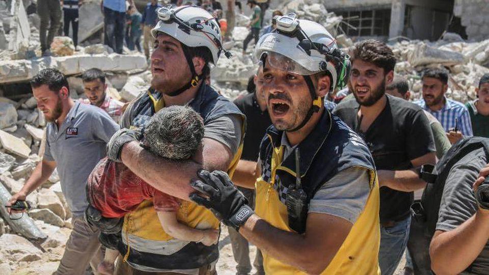 Weißhelme des syrischen Zivilschutzes tragen ein verletztes Kind aus den Trümmern eines zerstörten Gebäudes in der Provinz Idlib. Foto: Anas Alkharboutli/Archiv