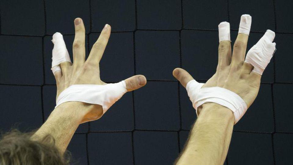 Blick auf die mit Tape umwickelten Finger eines Volleyballers. Foto: picture alliance / dpa/Symbolbild