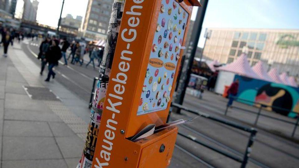 """""""Kauen, Kleben, Gehen"""" steht auf einer Klebewand für Kaugummis am Alexanderplatz. Foto: Paul Zinken/dpa/Archivbild"""