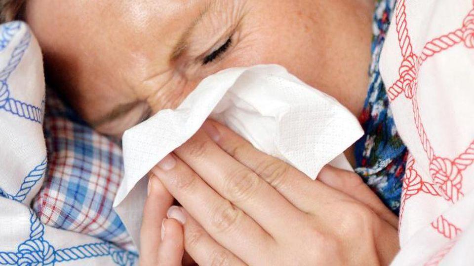 Eine Frau liegt im Bett und putzt sich die Nase. Foto: Maurizio Gambarini/dpa/Archiv