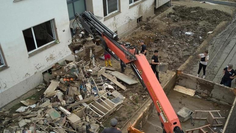 Ein Baukran arbeitet bei Aufräumarbeiten nach der verheerenden Flut. Foto: Thomas Frey/dpa