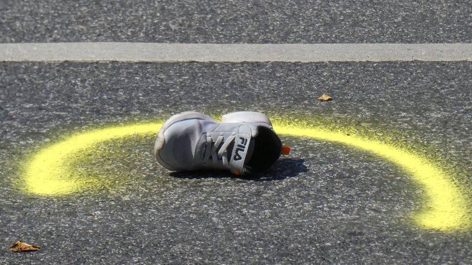 Ein Turnschuh liegt nach dem Unfall auf der Straße.