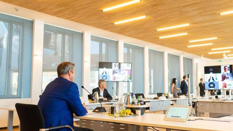 Der bayerische Ministerpräsident Markus Söder (CSU, l) und der bayerische Kultusminister Michael Piazolo (Freie Wähler, 2.v.l.) sitzen zur außerplanmäßigen Videokonferenz des bayerischen Kabinetts im Bayerischen Staatsministerium für Finanzen und für Heim