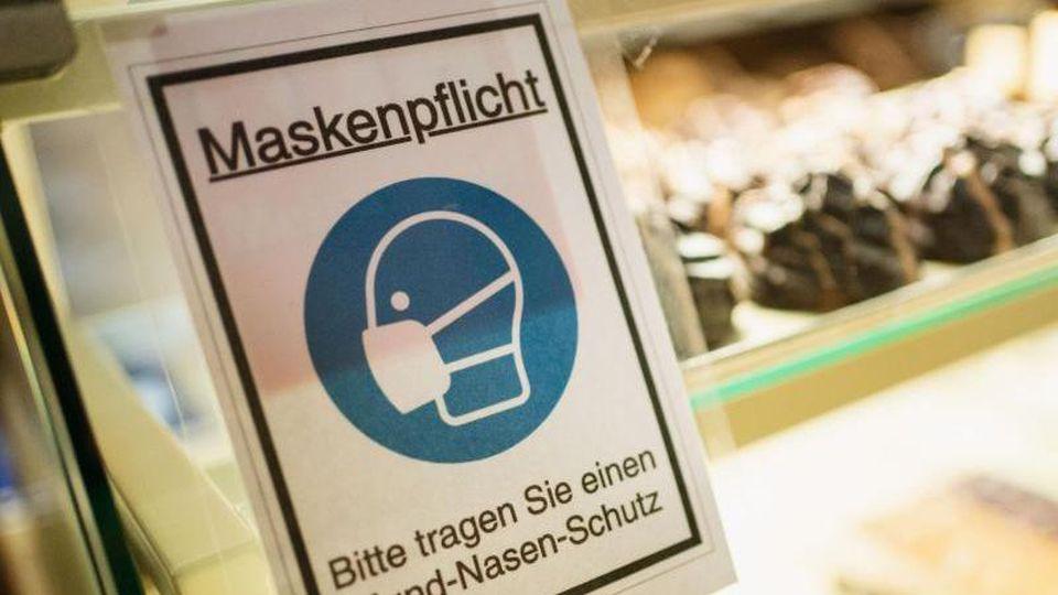 Ein Schild weist auf die Maskenpflicht hin. Foto: Nicolas Armer/dpa/Symbolbild