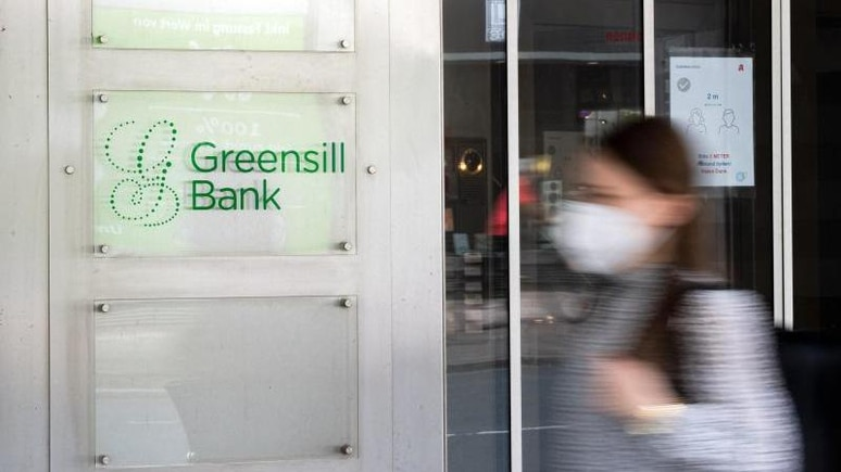 """Ein Schild mit dem Firmennamen """"Greensill Bank"""" hängt am Eingang der Bremer Privatbank. Foto: Sina Schuldt/dpa/Symbolbild"""