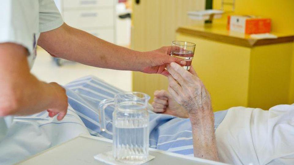 Eine Krankenpflegerin reicht einem Patienten in ein Glas Wasser. Foto: Daniel Karmann/dpa/Symbolbild
