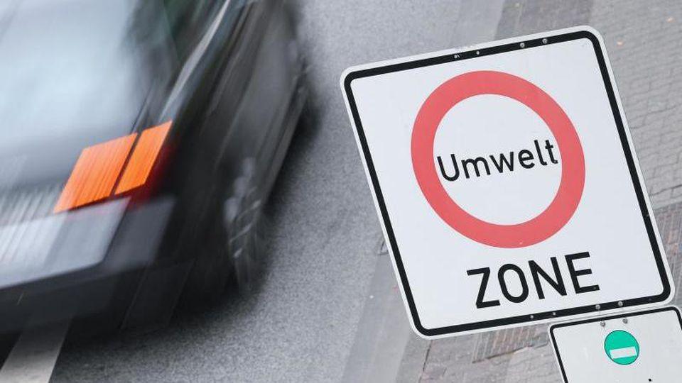 """Ein Auto fährt an einem """"Umwelt-Zone""""-Schild vorbei. Foto: Arne Dedert/dpa/Symbolbild"""