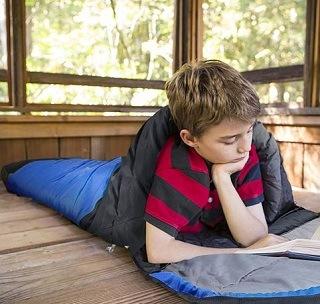 Ein Kind liest ein Buch im Schlafsack von Canway im Test und Vergleich